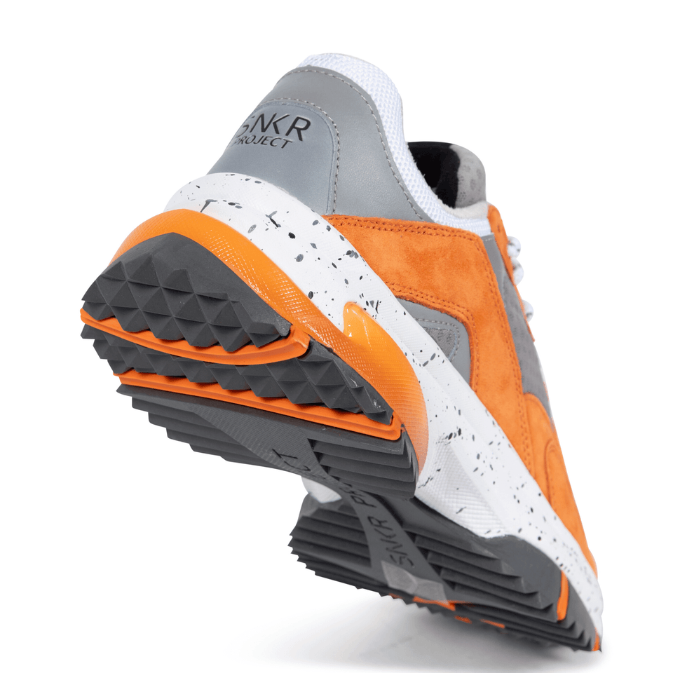The Prospect Park men's luxury sneaker with grey, orange and white mesh and suede. Comfortable speckled trail sole. sole of shoe