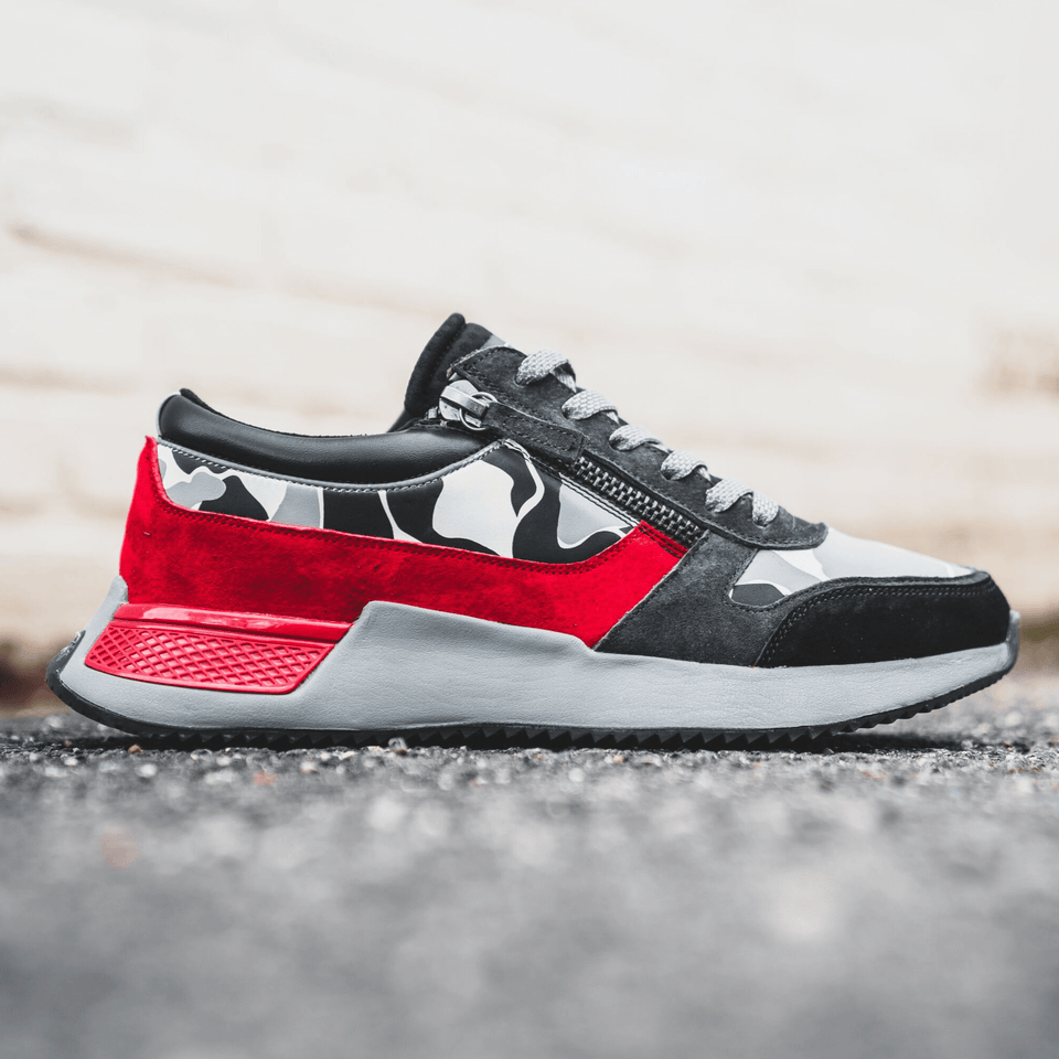The men's Rodeo 2.5 sneaker, red, grey camo, reflective laces, a functional side zipper and suede. Lifestyle image