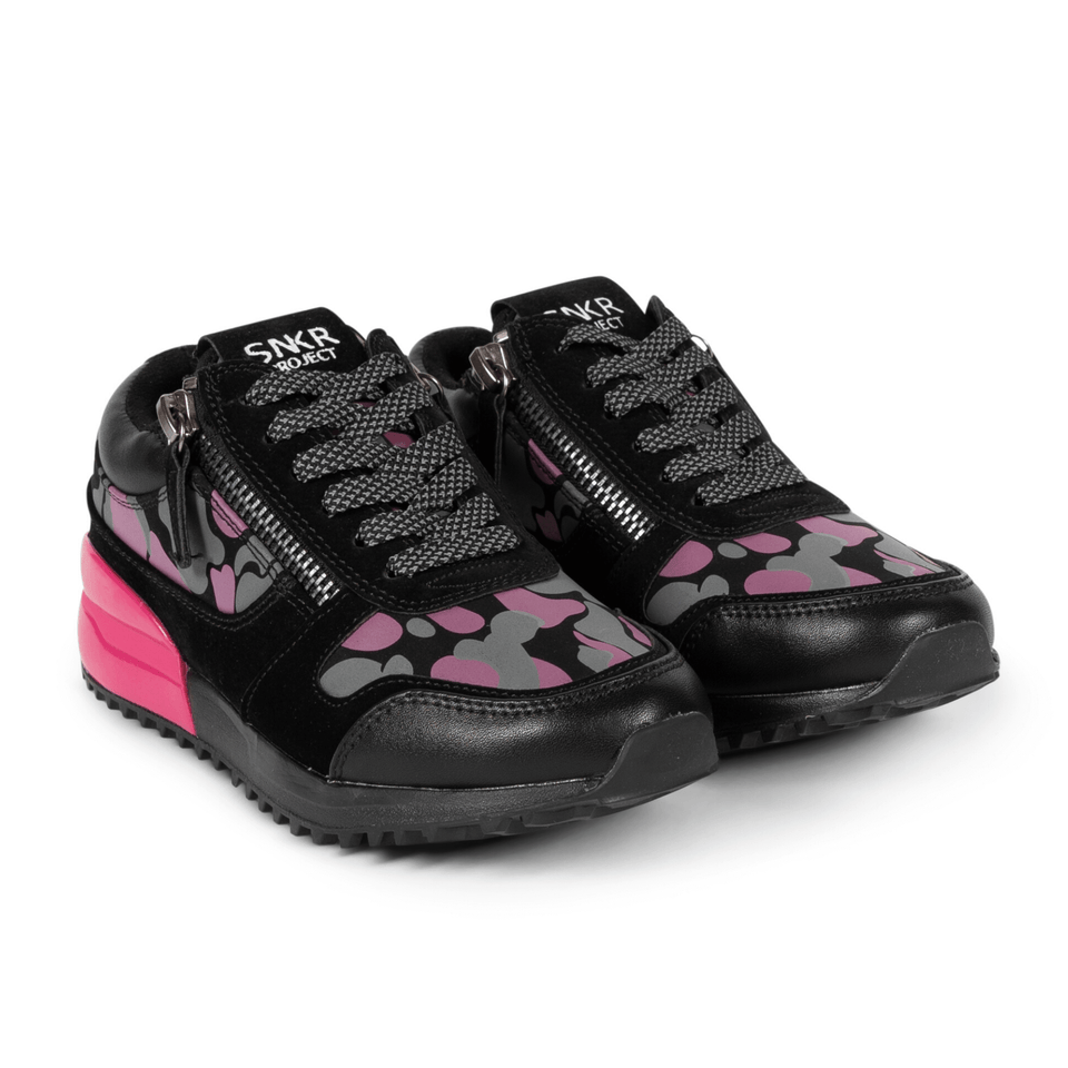 The Rodeo is a designer luxury black leather, women's sneaker. This athleisure shoe features a custom sole, pink camo, and zippers on the side. Two shoes.