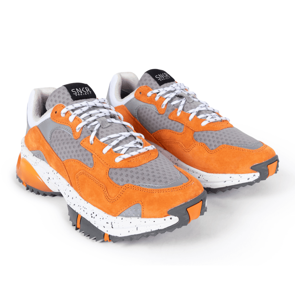 The Prospect Park men's luxury sneaker with grey, orange and white mesh and suede. Comfortable speckled trail sole. two shoes