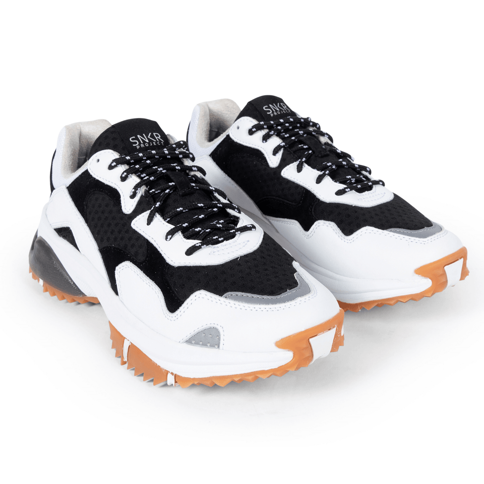 The Prospect Park men's luxury sneaker with black and white mesh and suede, silver accents. Comfortable gum trail sole. two shoes