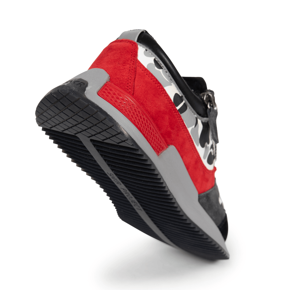 The men's Rodeo 2.5 sneaker, red, grey camo, reflective laces, a functional side zipper and suede. sole view