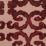 Detail of Amped Up Rug with a large curlie cue design in shades of  purple and red  on a pale pink field