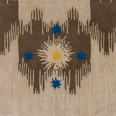 Detail of Estrella Rug in Quarry features a painterly abstract ikat in brown and taupe with star shaped accents in blue and yellow