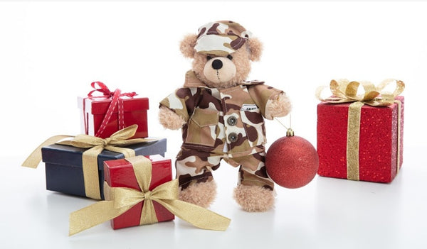 Teddy bear in military uniform in the middle of a set of gifts