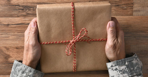 Soldier holding a gift wrapped in brown paper and red and white ribbon