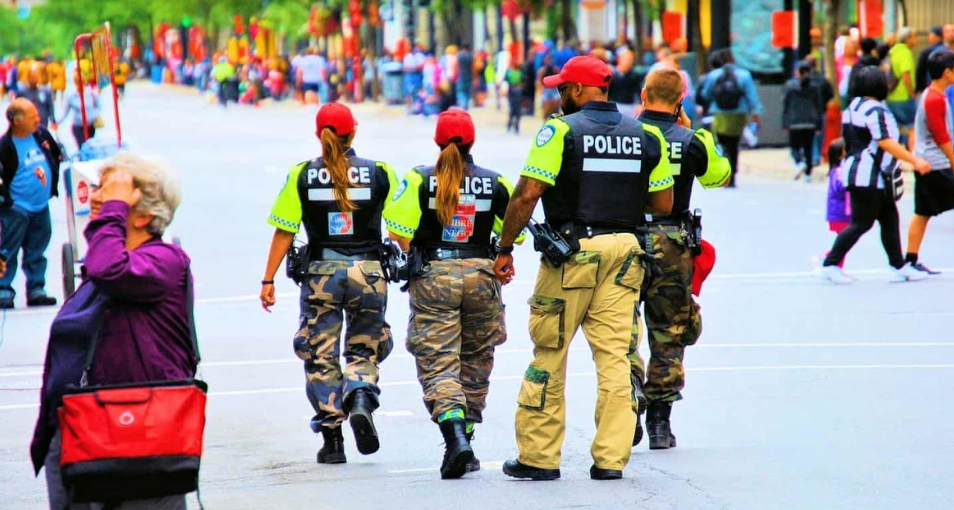 Four police officers patrolling a busy street wearing bulletproof vests