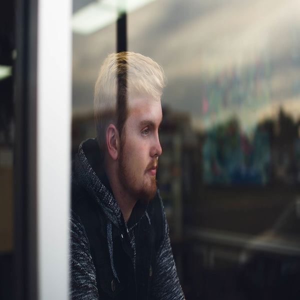 A blonde, bearded man staring out the window