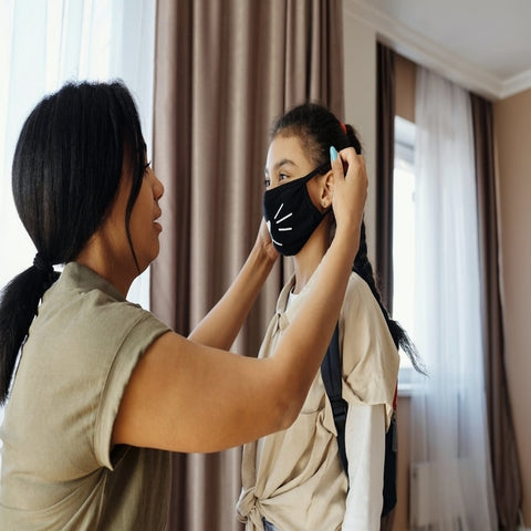 Woman putting on a black cat face mask to a little girl
