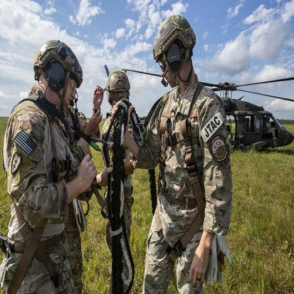 A group of soldiers standing near a helicopter having a discussion about ropes
