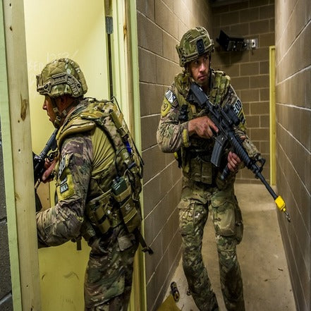 Two soldiers clearing a room in a close quarters battle situation