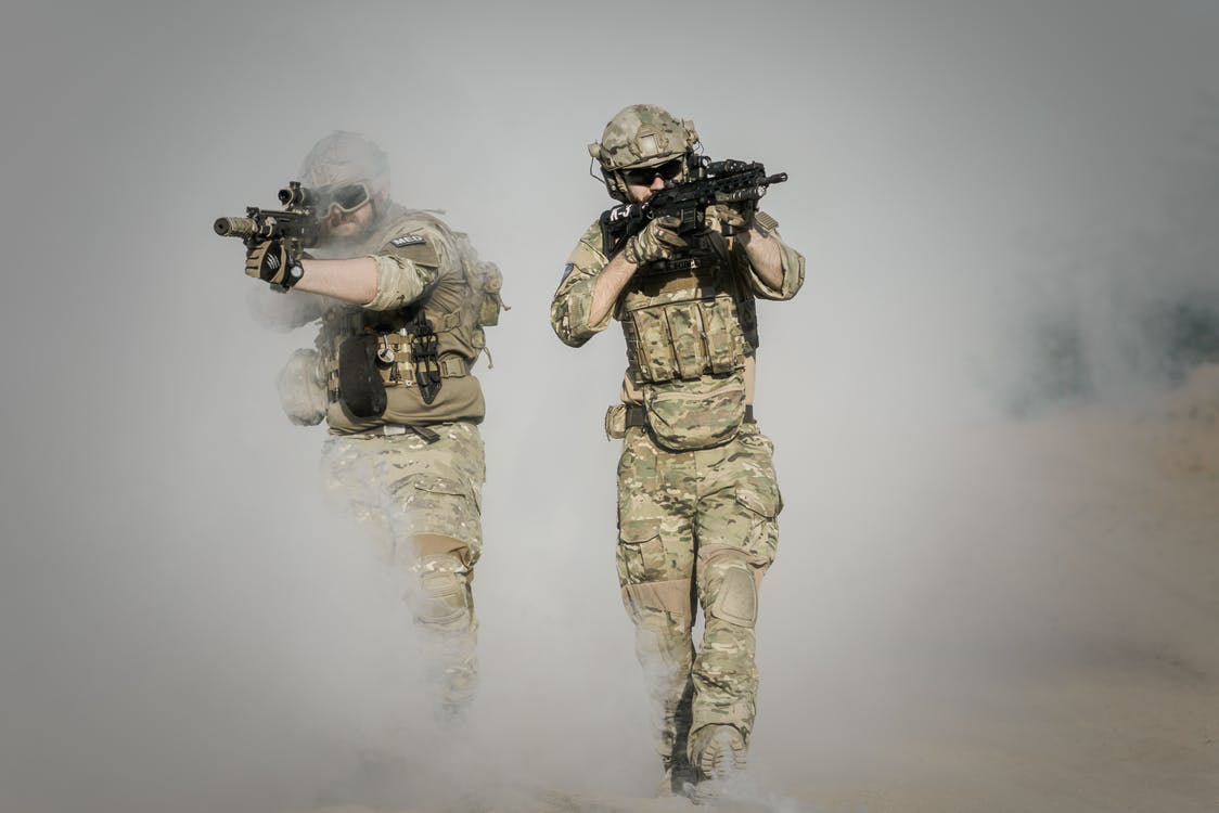soldiers in camo with guns