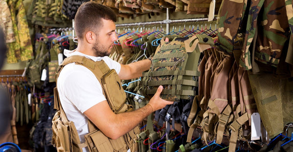 Man inspecting a multicam plate carrier in a body armor shop
