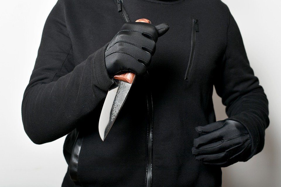 image of a man in dark clothing  holding a knife