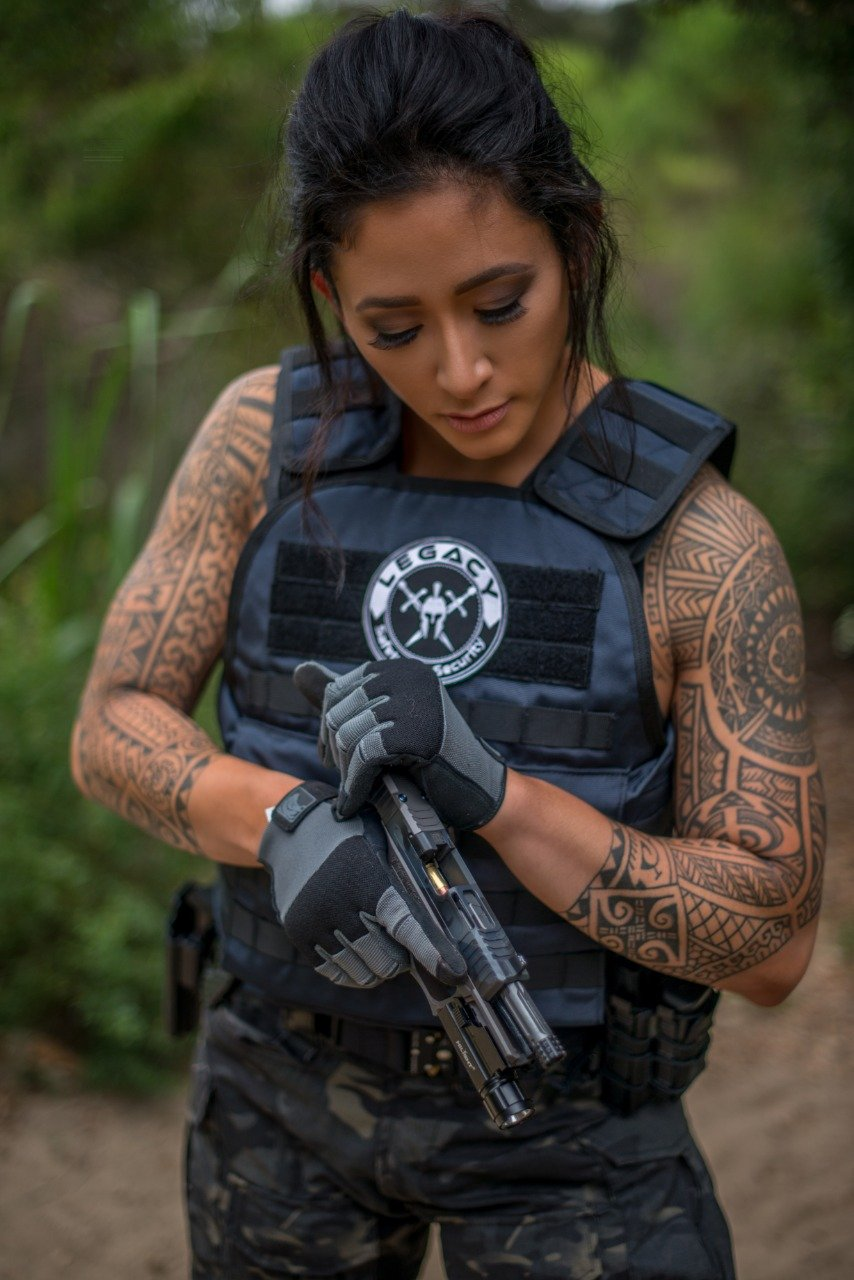 Tattooed woman with a gun wearing Legacy Safety and Security bulletproof vest