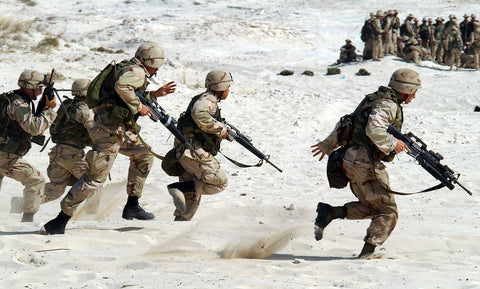image of soldiers in body armor running through sand