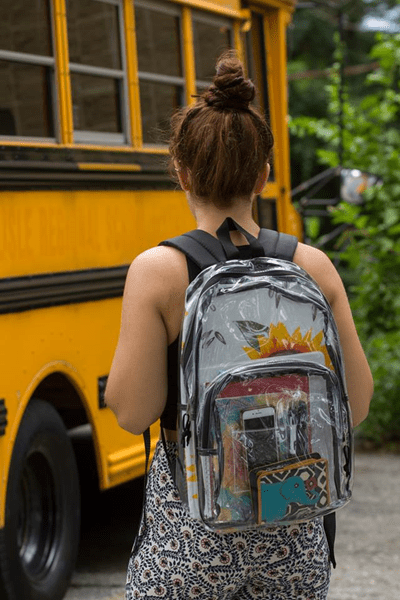 Image of a girl wearing a backpack walking toward a school bus