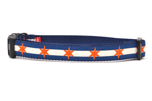 Large dog collar has two outer dark blue stripes and one central off-white stripe and orange six point stars around the collar.