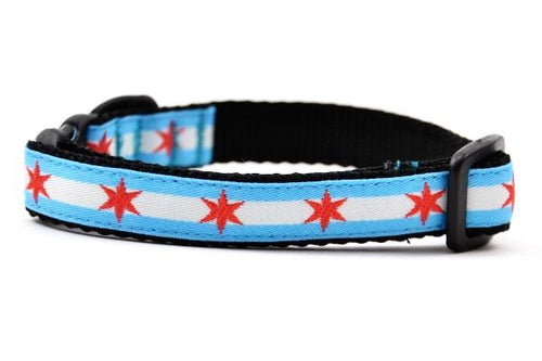 Cat collar with two light blue stripes and one white stripe and red six pointed stars - representing the Chicago Flag.