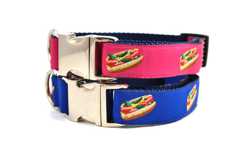 Two stacked collars with metal clasps- one navy and one raspberry with design that depicts the Chicago Style Hot Dog.