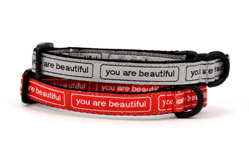 Two cat collars stacked.  One is silver with the words you are beautiful in black.  One is red with the words you are beautiful in white.
