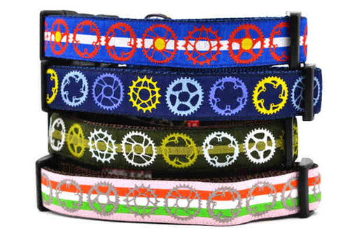 Stack of four dog collars with bicycle sprocket designs.  One is pink with red, white, and green stripes and gray sprockets.  One is green with light green stripe and white, light green, and light blue sprockets.  One is navy with yellow, purple, and gray sprockets.  One has the colors of the colorado flag.