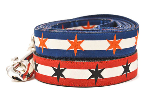 Two Large dog collars stacked.  One has two outer red stripes and one central off-white stripe and black six point stars around the collar. One has two outer dark blue stripes and one central off-white stripe and orange six point stars around the collar.