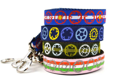 Stack of four dog leashes with bicycle sprocket designs.  One is pink with red, white, and green stripes and gray sprockets.  One is green with light green stripe and white, light green, and light blue sprockets.  One is navy with yellow, purple, and gray sprockets.  One has the colors of the colorado flag.
