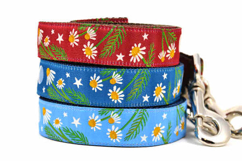 Stack of three dog leashes - one light blue, one dark teal, and one burgundy.  Each collar as the same design which depicts chamomile flowers, stars, and a half moon.