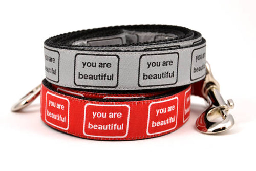 Two dog leashes stacked.  One is red with the words you are beautiful in white.  One is silver with the words you are beautiful in black.