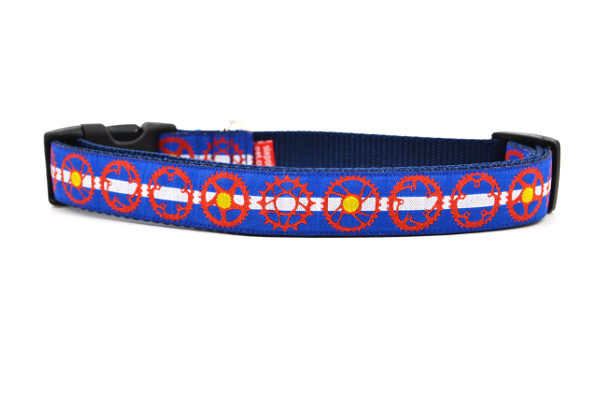 Large dog collar with light blue and white stripe, red bicycle sprockets - some filled in with yellow.  Emulating the colors of the colorado state flag.