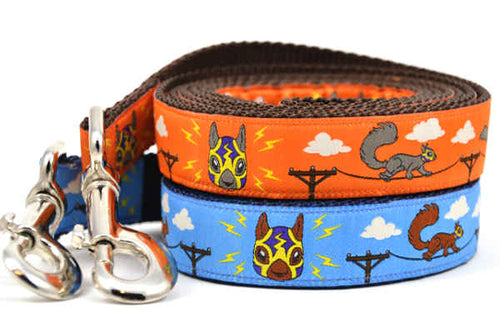 Two large dog leashes - one orange and one light blue - design includes squirrels running on telephone wires and squirrel in lucha libre mask.  The mask is purple and yellow with electrical sparks coming from the mask.