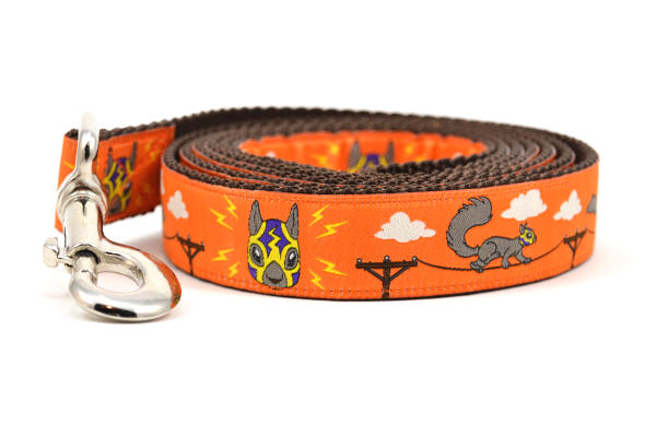 One large orange dog leash - design includes squirrels running on telephone wires and squirrel in lucha libre mask.  The mask is purple and yellow with electrical sparks coming from the mask.