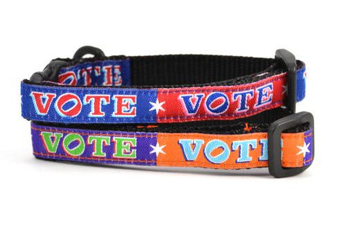 Two cat collars shown stacked.  One is red and navy blocks pattern with the word VOTE on each color block.  One is purple and orange blocks pattern with the word VOTE on each color block.