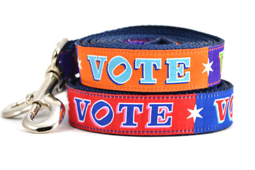 Two dog leashes stacked.  One is purple and orange blocks pattern with the word VOTE on each color block. One is red and navy blocks pattern with the word VOTE on each color block.