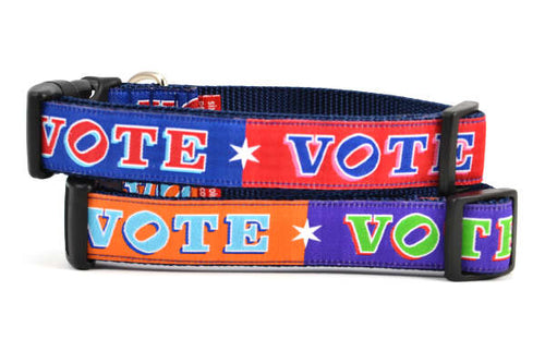 Two dog collars stacked. One is red and navy blocks pattern with the word VOTE on each color block. One is purple and orange blocks pattern with the word VOTE on each color block.