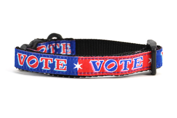 Cat collar that is red and navy blocks pattern with the word VOTE on each color block.