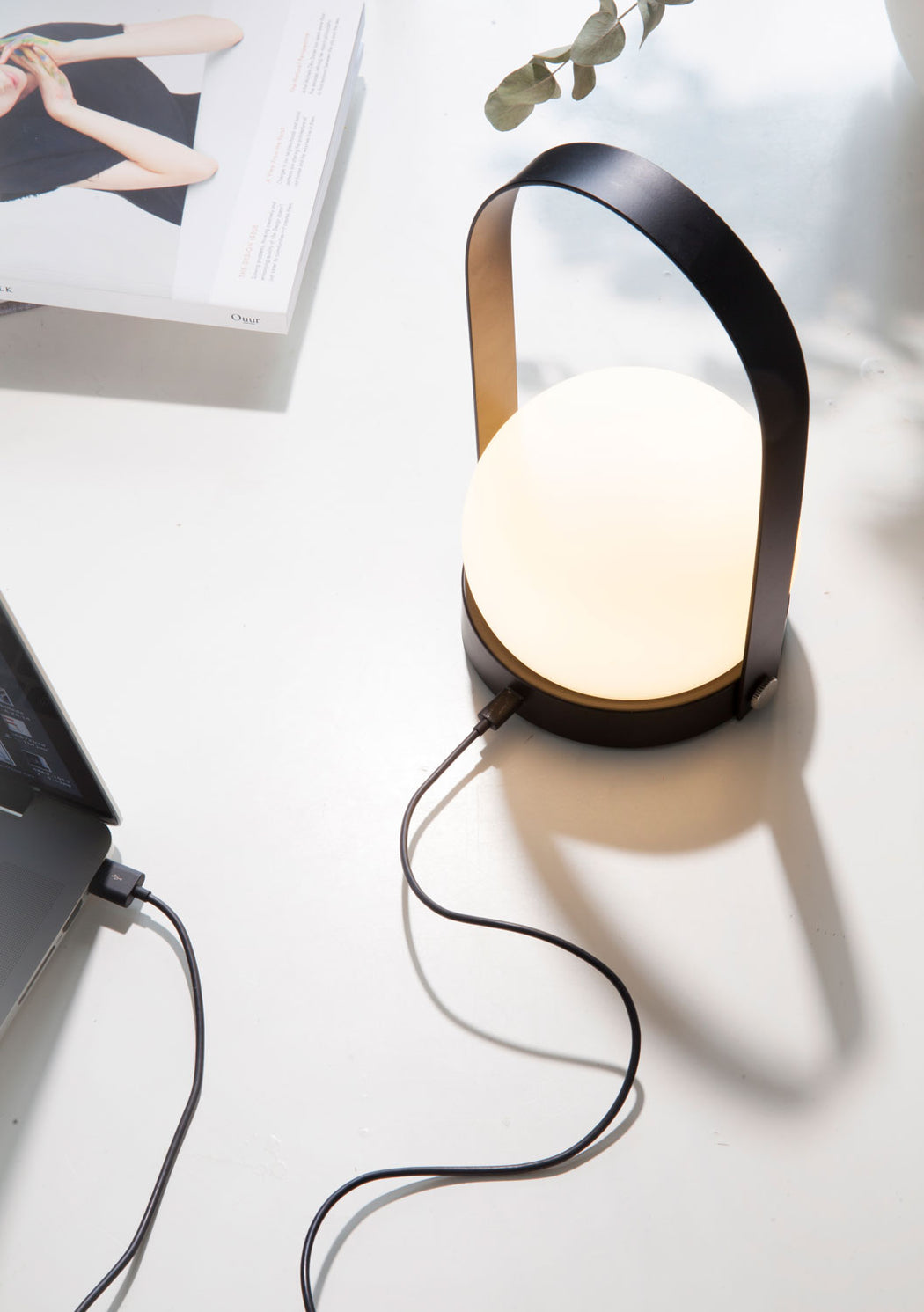Carrie LED Table Lamp in Black being charged