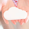 Two hands holding a white cloud bath bomb
