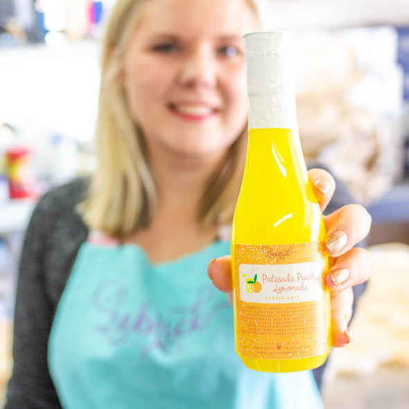 Alicia, owner showing a bottle of Palisade Peach Bubble Bath