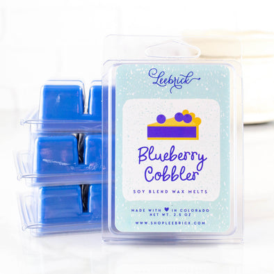 Three packages of blueberry cobbler stacked up behind another package of wax melts