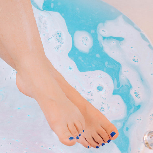 Woman's feet above blue bath water.