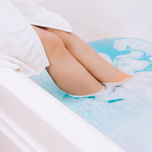 woman's legs soaking in blue bathwater
