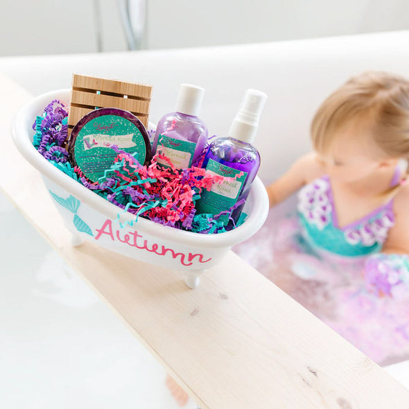 Little girl in bath with mermaid Kisses bathtub gift basket