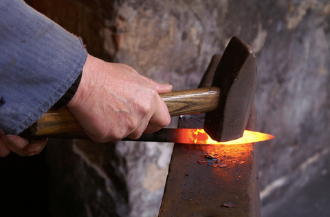 blacksmith using heat to flatten metal
