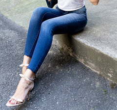 model sitting on curb wearing High Rise Ankle Skinny Stretch Jean