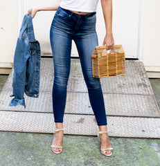 torso of model wearing High Rise Ankle Skinny Stretch Jean holding jean jacket and bamboo bag