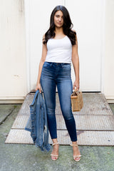 model wearing High Rise Ankle Skinny Stretch Jean holding jean jacket and bamboo bag