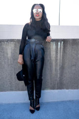 Model leaning on concrete wall wearing black Vegan Leather Paper Bag Pants
