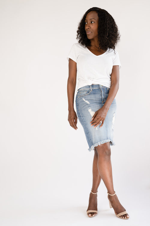 Model poses with crossed legs wearing Distressed Denim Mini Skirt